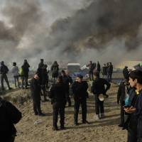 Migrants, police and media stand on a hill overlooking shelters burning in the makeshift migrant camp near Calais, northern France, Wednesday. French authorities declared the Calais migrant camp known as 'the Jungle,' empty on Wednesday, after fires set by departing migrants accelerated plans to evacuate the burgeoning slum. | AP