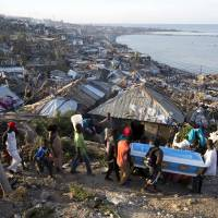 Haitians carry a coffin containing a pregnant victim of Hurricane Matthew in Jeremie on Friday. | AP