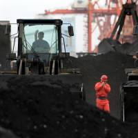 An employee walks between front-end loaders used to move coal imported from North Korea at Dandong port in the Chinese border city of Dandong on Dec. 7, 2010. | REUTERS