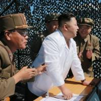 North Korean leader Kim Jong Un supervises a demonstration of a new rocket engine for a satellite at the Sohae Space Center in this undated photo released on Sept. 20. | KCNA / VIA REUTERS