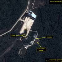 Satellite imagery taken Oct. 1 shows crates on the launchpad next to the gantry tower and vehicles near the fuel and oxidizer buildings at the Sohae satellite launching station in North Korea. | AFP-JIJI