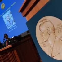 A portrait of 2016 Nobel Prize in medicine winner Yoshinori Ohsumi of Japan is displayed behind members of the 2016 Nobel Committee for Physiology or Medicine during a news conference in Stockholm on Monday. | AFP-JIJI