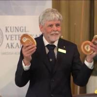 A screenshot of a live broadcast of the Nobel Prize announcement in which Thors Hans Hansson, a member of the Nobel committee for physics, explains concepts of topology using a cinnamon bun, a bagel and a pretzel. | SOURCE: NOBELPRIZE.ORG / FACEBOOK