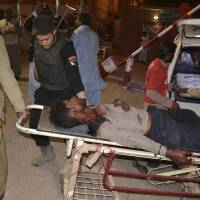 Volunteers rush an injured person to a hospital in Quetta, Pakistan, late Monday after gunmen attacked a police training center in Pakistan's restive southwestern Baluchistan province. | AP