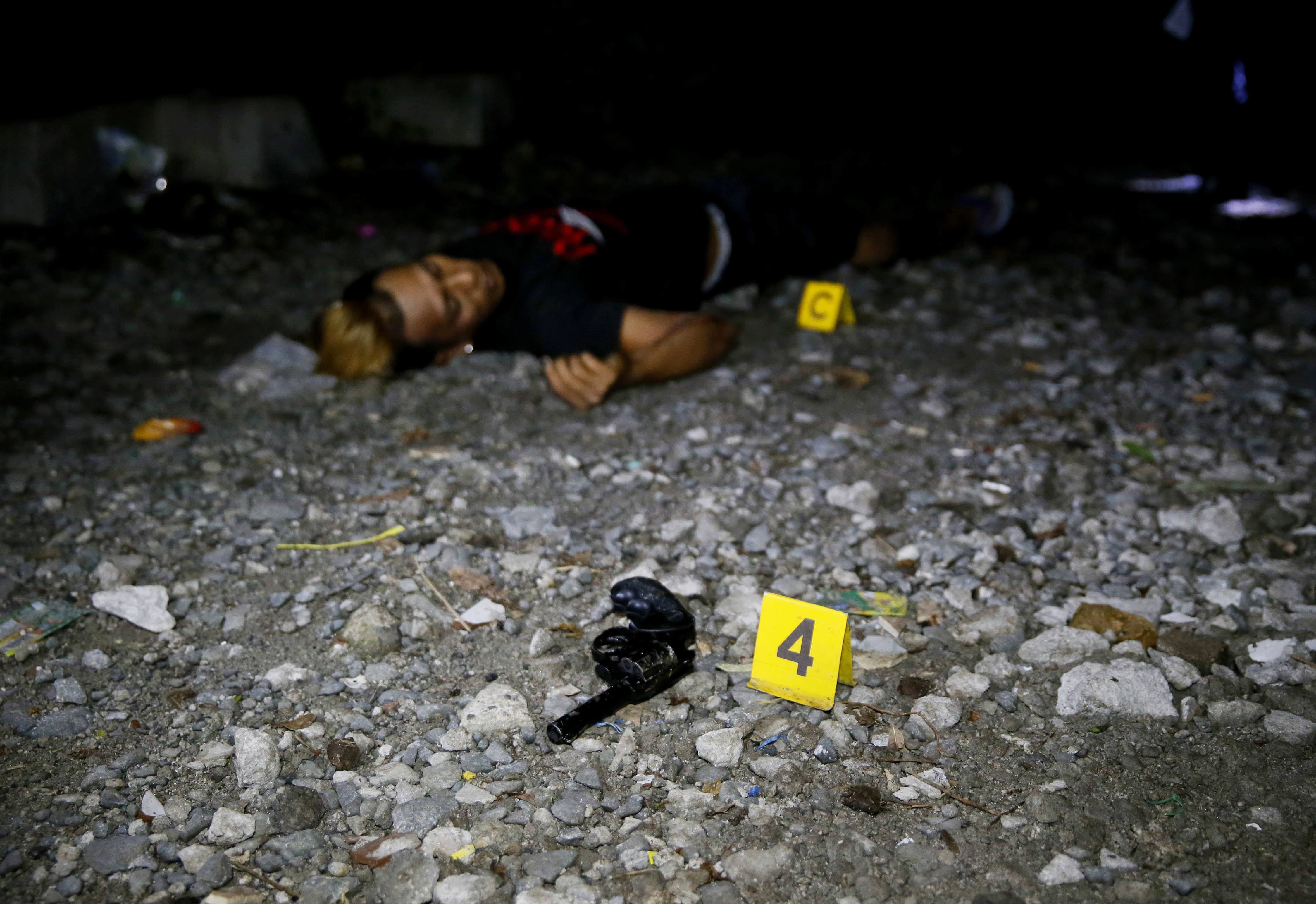 A pistol lies near the body of a drug suspect who was killed with two others in an alleged 'buy-bust' operation before dawn on Friday in Caloocan city, north of Manila, in the continuing 'war on drugs' campaign of President Rodrigo Duterte.   AP