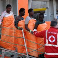 Women disembark in Sicily from the Siem Pilot on Monday after rescue operations of migrants at sea during the weekend. | AFP-JIJI