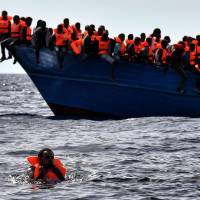 Migrants wait to be rescued as they drift in the Mediterranean some 20 nautical miles north off the coast of Libya on Monday. Italy coordinated the rescue of more than 5,600 migrants off Libya, three years to the day after 366 people died in a sinking that first alerted the world to the Mediterranean migrant crisis. | AFP-JIJI