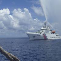 Philippines says China still guarding key shoal but Filipino fisherman back