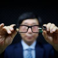 Moon Seoung-ok, president of the Headquarters of Reporting for Public Good, shows a pair of glasses fitted with a camera during a class in Seoul on Friday. | REUTERS