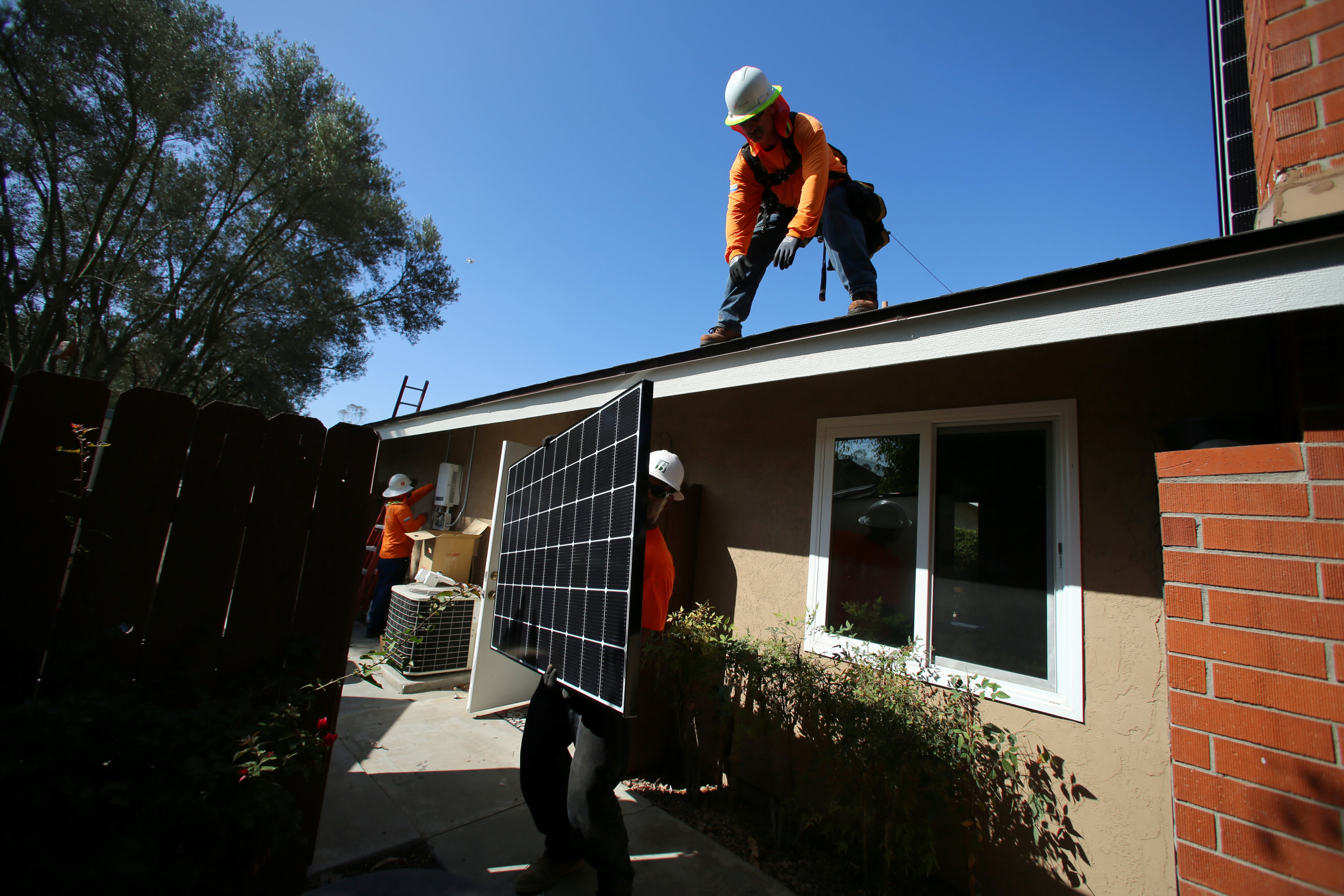 Workers install solar panels on the roof of a home in Scripps Ranch, northeastern San Diego, on Oct. 14. | REUTERS