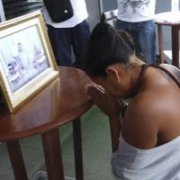 Thai police force woman to kneel before late king's photo for alleged insult