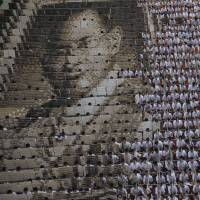 Some 1,000 students practice flipping boards with photos to reveal a full-mosaic portrait of the late Thai King Bhumibol Adulyadej at Assumption College in Bangkok last Friday. | AP
