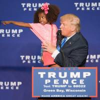 Republican U.S. presidential nominee Donald Trump holds a child as he speaks during a rally in Green Bay, Wisconsin, on Monday. | AFP-JIJI