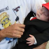 Three-month old Matthew Cohen is dressed in a Donald Trump-style suit by his father, Les Cohen, of Victorville, California, before the start of Republican presidential candidate Donald Trump's rally on Wednesday at the Henderson Pavilion in Henderson, Nevada. | AFP-JIJI