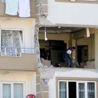 A police officer inspects a damaged apartment at the explosion site Sunday near the Syrian border in Gaziantep after a bomber blew himself up. | AFP-JIJI