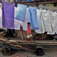 Children play on a handcart inside a slum in Mumbai on Tuesday. | REUTERS