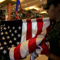 U.S. Marines roll the American flag after the PHIBLEX Philippines-U.S. amphibious landing exercise closing ceremony in Taguig city, Metro Manila, on Oct. 11. | REUTERS