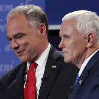 Democratic U.S. vice presidential nominee Tim Kaine (left) and Republican U.S. vice presidential nominee Mike Pence pat each other on the back at the conclusion of their vice presidential debate at Longwood University in Farmville, Virginia, on Tuesday. | REUTERS