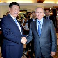 Russian President Vladimir Putin shakes hands with Chinese President Xi Jinping during their meeting in Benaulim, in the western state of Goa, India, on Saturday. | REUTERS