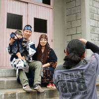 Hope for a new generation: Taka Maesawa takes a photograph of Megumi Kawakami and her family in the town of Makubetsu, Hokkaido, in August. | KYODO