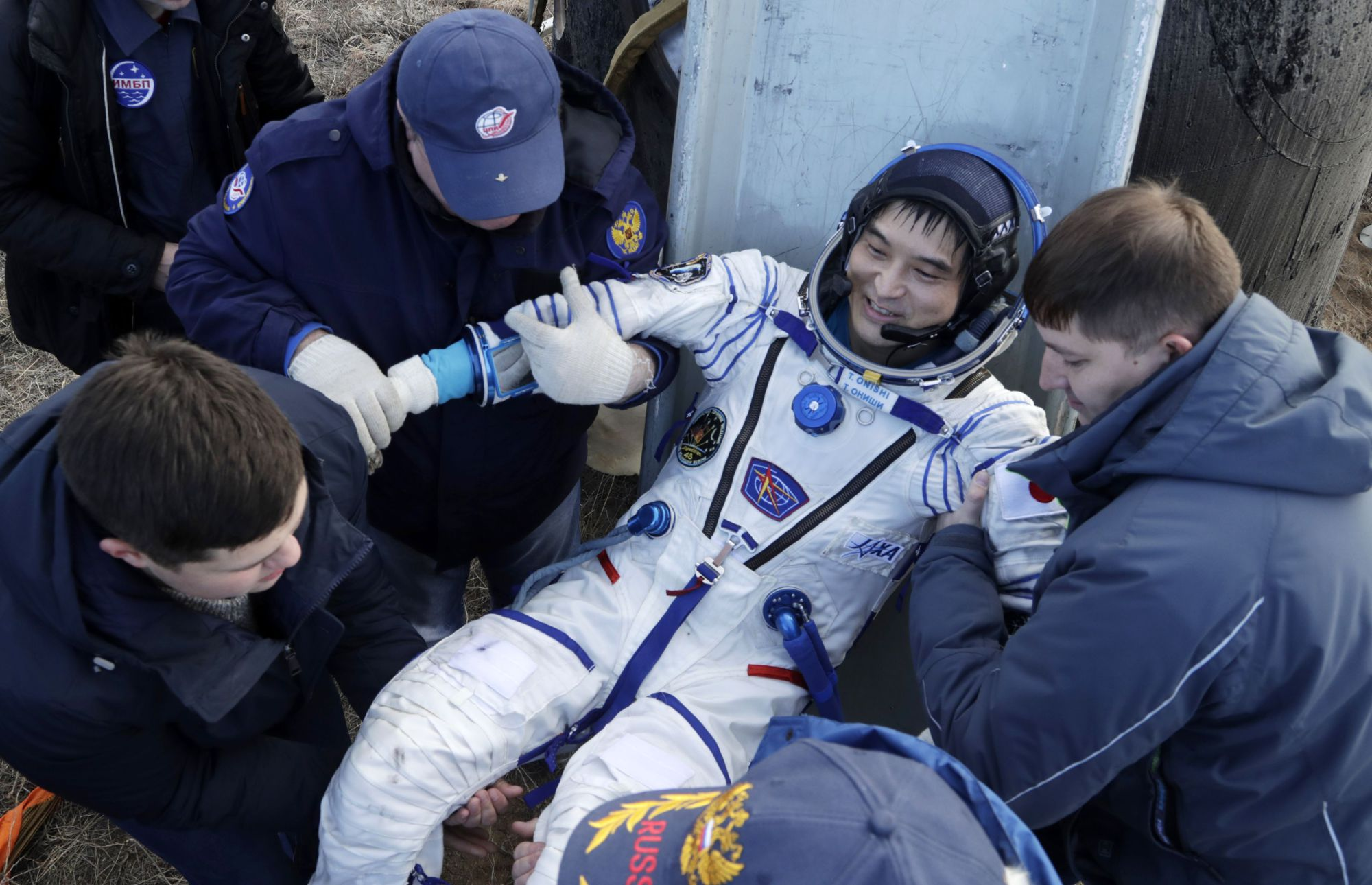 Astronaut Takuya Onishi of Japan is helped out of a Russian spacecraft that landed in Kazakhstan on Sunday. He and two other astronauts spent nearly four months aboard the International Space Station. | AFP-JIJI