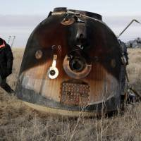 A Russian Soyuz MS space capsule is shown after landing about 150 km southeast of the Kazakh town of Zhezkazgan on Sunday. A rescue helicopter can be seen behind. | AFP-JIJI