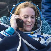 NASA astronaut Kate Rubins talks to her family via satellite phone shortly after being helped out of a Soyuz spacecraft that landed near the town of Zhezkazgan in central Kazakhstan on Sunday. | AP