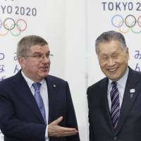 International Olympic Committee President Thomas Bach (left) and Tokyo 2020 Olympic Organizing Committee President Yoshiro Mori chat prior to a press briefing in Tokyo on Oct. 19. | AP