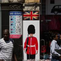 A pedestrian passes a souvenir shop with currency exchange sign at London's Piccadilly Circus in July. | BLOOMBERG