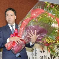 Jiro Hatoyama, backed by the Liberal Democratic Party, holds a victory bouquet Sunday in Kurume, Fukuoka Prefecture, after winning a Lower House by-election. | KYODO
