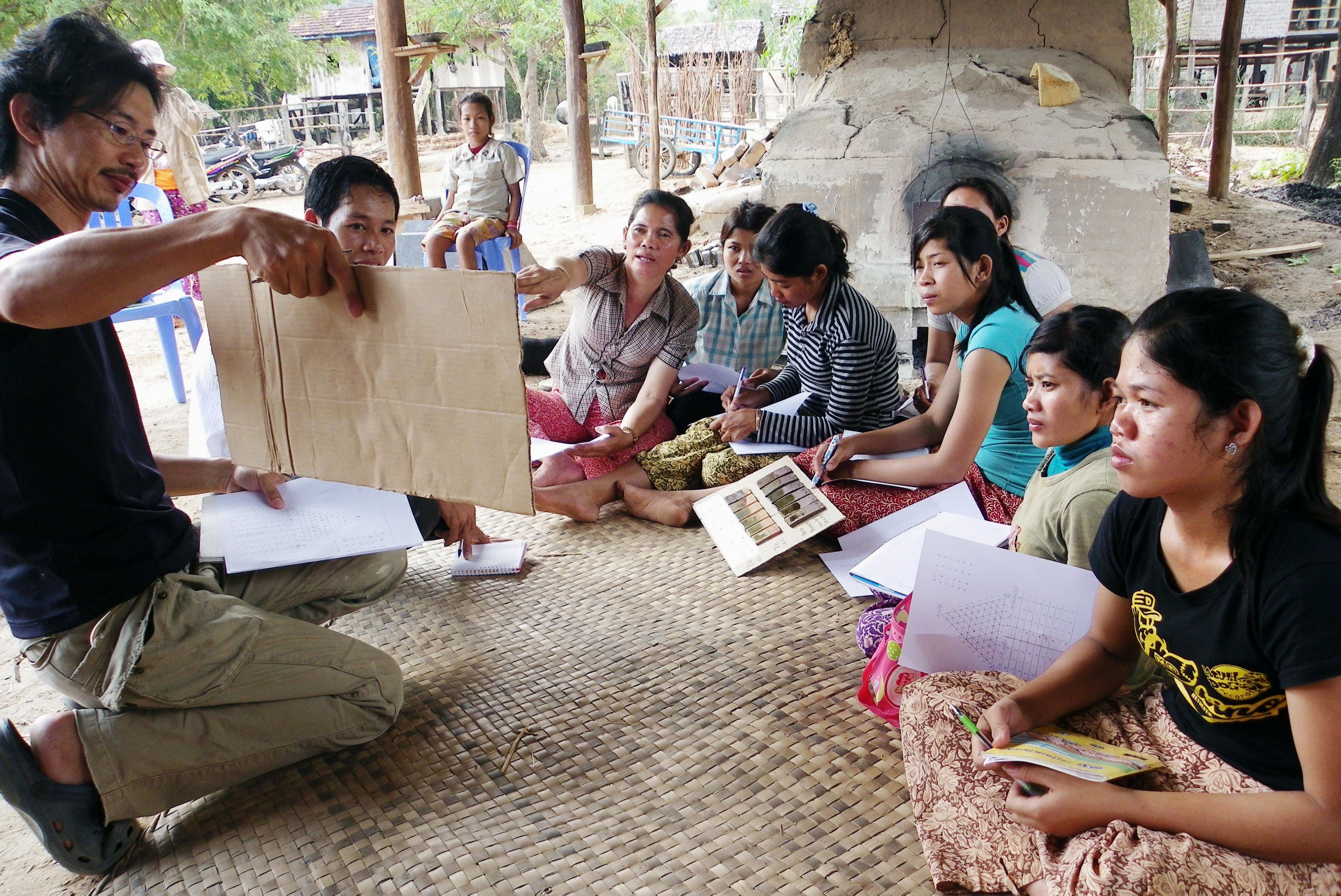 Shinsuke Iwami (left) explains how to glaze ceramics to Cambodian potters at a village in the central Cambodian province of Kampong Chhnang in February 2010. | SHINSUKE IWAMI / VIA KYODO