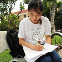 Do Thi Hang, 23, studies Japanese in a Hanoi park in July. | KYODO