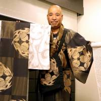 Designer Nobuaki Tomita shows off kimono dyed with chocolate at his workshop in Kyoto last month. | KYODO