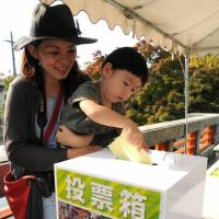 A mother and her son vote to determine the most popular animal at Higashiyama Zoo and Botanical Gardens in Nagoya in October. | CHUNICHI SHIMBUN