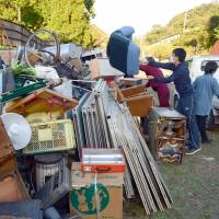 Residents of Kurayoshi, Tottori Prefecture, bring household items damaged by last week's earthquake to a temporary disposal site on Monday. | KYODO