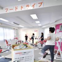 Members of fitness club Fits Me Idogaya in Yokohama participate in a food drive at a gym Aug. 4. | KYODO
