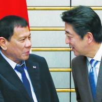 Philippine President Rodrigo Duterte is greeted by Prime Minister Shinzo Abe at the start of their meeting in Tokyo on Wednesday. | POOL / VIA AFP-JIJI