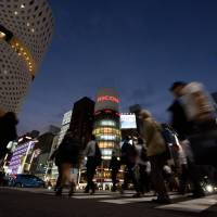 Pedestrians cross a street in Tokyo's Ginza district on Sept. 27. The government and Keidanren plan to launch a 'Premium Friday' campaign to perk up sluggish consumption. | BLOOMBERG