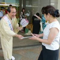 Kyoto Mayor Daisaku Kadokawa distributes traditional fans in the city in July 2014 to promote a maglev route that passes through the ancient capital. | KYODO
