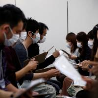 Participants wearing surgical masks converse during a masked match-making event held in Tokyo on Sunday. | REUTERS