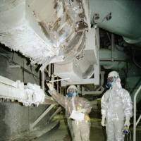 Workers inspect the Monju plant after a sodium leak in December 1995. | KYODO