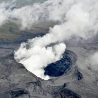 Smoke rises from a crater on Mount Aso in Kumamoto Prefecture after the volcano belched a column of ash 11,000 meters into the air early Saturday. | KYODO
