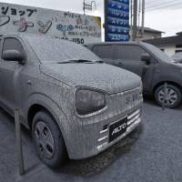 Ash from Mount Aso's eruption covers vehicles parked in the city of Aso, Kumamoto Prefecture, early on Saturday. | KYODO