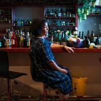 Yoko Matsumoto, owner of the Apple Pie bar, sits inside her store in the town of Namie, Fukushima Prefecture, on Oct. 5. Access to the town is still severely restricted due to radiation contamination resulting from the March 2011 disaster.   BLOOMBERG