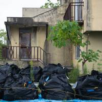 Bags of nuclear waste sit in front of an abandoned house in Namie, Fukushima Prefecture, on Oct. 5. | BLOOMBERG