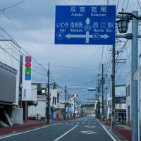 A traffic sign stands on an empty street in Namie, Fukushima Prefecture, on Oct. 5. | BLOOMBERG