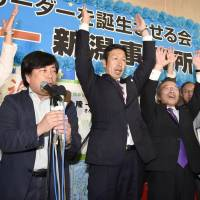 Ryuichi Yoneyama (center), a medical doctor who advocates anti-nuclear policies, raises his hands as supporters shout 'banzai' after he was assured of winning Sunday's gubernatorial election in Niigata Prefecture. | KYODO