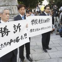 Families of the victims of the 2011 tsunami that hit Okawa Elementary School in Ishinomaki, Miyagi Prefecture, hold up a sign Wednesday that says they won the suit and the children's voices were heard, in front of the Sendai District Court. | KYODO