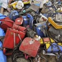 School backpacks and other belongings of the victims of the 2011 tsunami are collected in Ishinomaki, Miyagi Prefecture. | KYODO