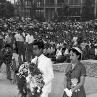 Prince Mikasa and his wife, Princess Yuriko, lay flowers at the cenotaph for atomic-bomb victims during a peace memorial ceremony in Hiroshima in this file photo from Aug. 6, 1957. | KYODO